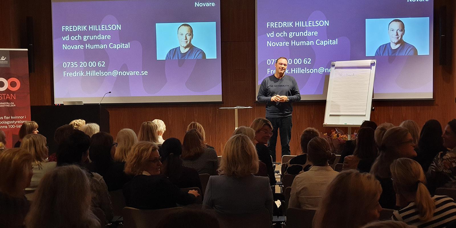 Fredrik Hillelson framför två stora skärmar vid en konferens