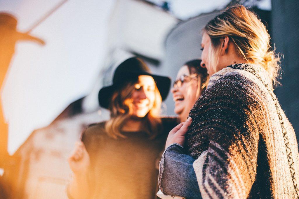 Tre glada kvinnor skrattar