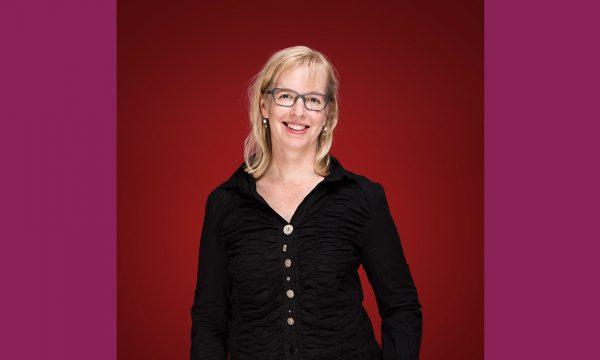 Maria Frej framför röd bakgrund