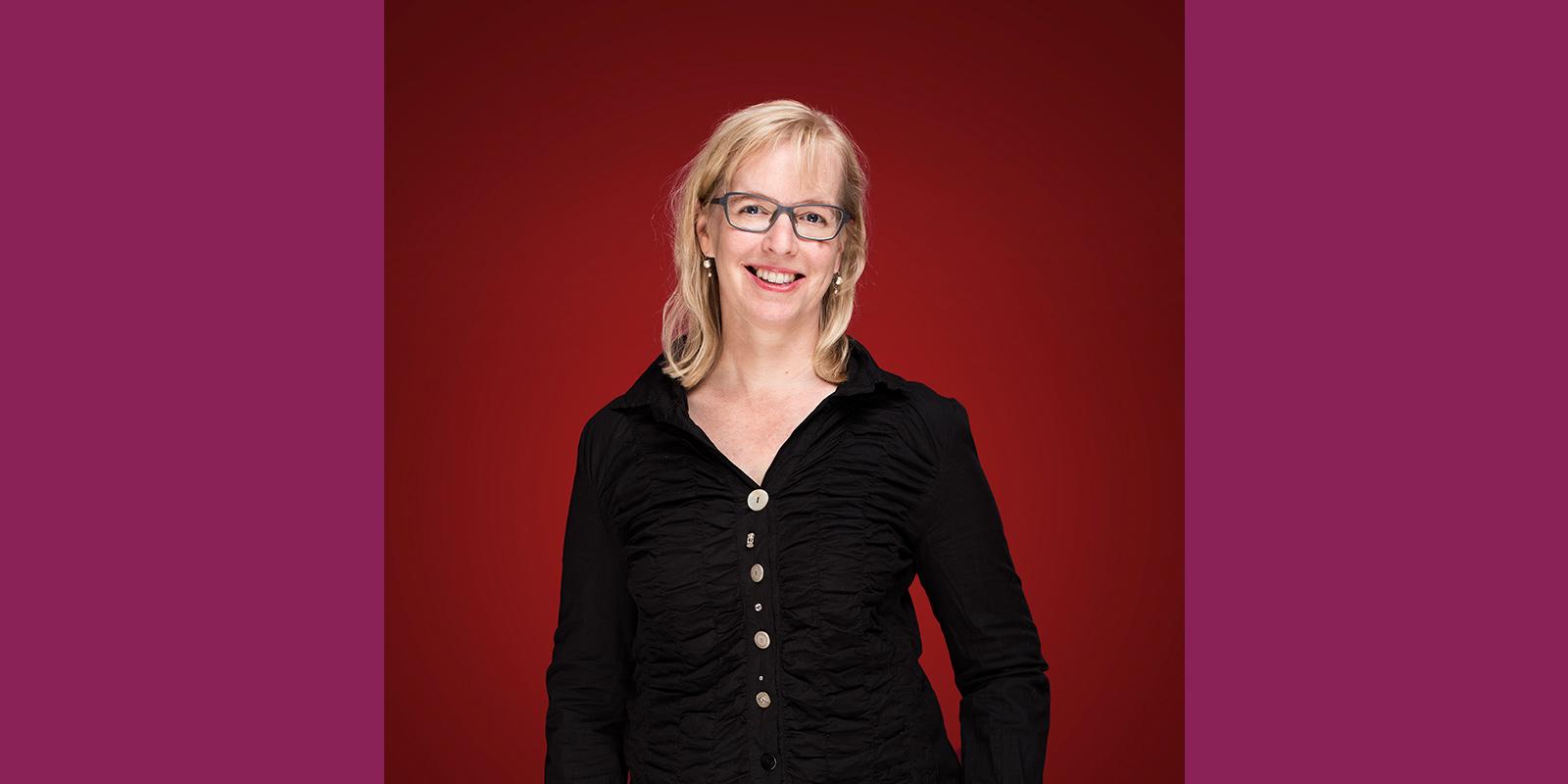 Maria Frej framför en röd bakgrund